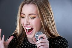 Portrait of a beautiful blonde young woman singing into microphone Stock Photos