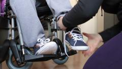 Helping a disabled young man in wheelchair - stock footage