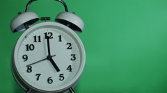 Ringing classical alarm clock at five o'clock,  green background Stock Footage