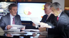 4K Mature male businessmen in a meeting analysing figures and statistics - stock footage