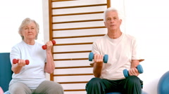 Active seniors lifting hand weights Stock Footage