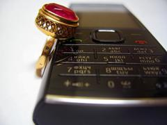 Mobile phone and golden ring with red stone - stock photo