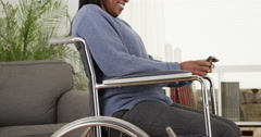Disabled senior black woman using smartphone in chair Stock Footage