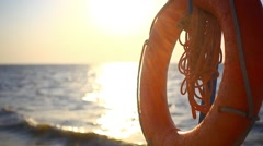 Lifebelt on beautiful beach during amazing sunset in slow motion. Rays of the Stock Footage