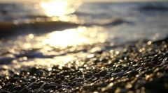 Colorful pebbles on the beach at amazing sunset with sea view, splashes waves Stock Footage