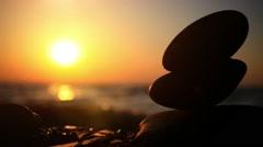 Stones pyramid on pebble beach symbolizing zen, harmony, balance. Sea at sunset - stock footage