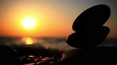 Stones pyramid on beach symbolizing zen, harmony, balance. Sea at sunset in the Stock Footage