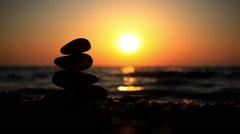 Stones pyramid on beach symbolizing zen, harmony, balance. Sea at sunset in the - stock footage
