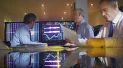 4K Mature male stock brokers in a meeting, looking at the world markets - stock footage