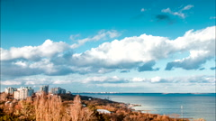 Moving clouds in the sea and city. Time lapse - stock footage