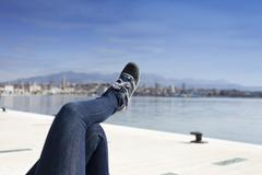 Legs in jeans pants and blue sport shoes on sea coast Stock Photos