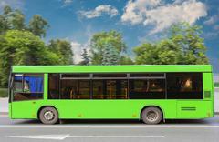 City bus moves down the street Stock Photos