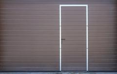 metal gate of garage with door - stock photo