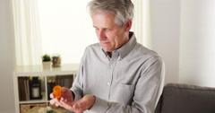 Senior man taking prescription tablets Stock Footage