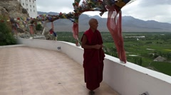 Buddhist Monk Walking Past Pray Flags and Stupas.mp4 Stock Footage