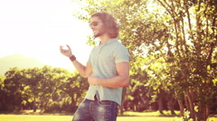 In high quality 4k format young man playing air guitar in the park Stock Footage