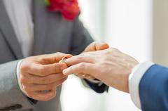Close up of male gay couple hands and wedding ring Stock Photos