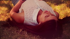 In high quality 4k format pretty brunette lying on grass Stock Footage