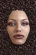 pretty girl's face immersed in coffee beans - stock photo