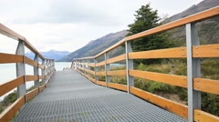 Tourist walking on Perito Moreno footbridge by Argentino lake - stock footage