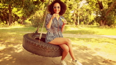 In high quality 4k format pretty young woman in tire swing Stock Footage
