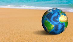 Earth globe on the sea beach (Elements of this image furnished by NASA) - stock photo