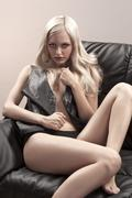 young blonde posing on a sofa - stock photo
