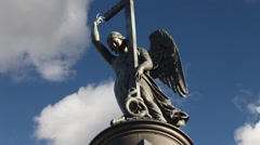 Statue of winged angel with cross in blue sky Stock Footage