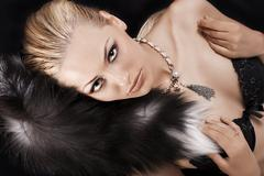 sexy blonde laying on black just wearing fur - stock photo
