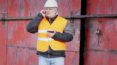 Worker  talking on cell phone near the metal door - stock footage