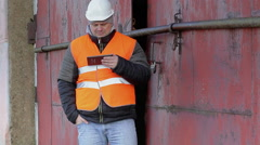 Worker with tablet PC near the red metal door - stock footage