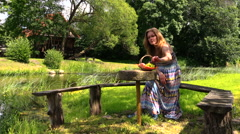 Happy pregnant woman have picnic on bench near river water Stock Footage