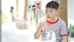 Little asian boy eating snack at home - stock footage
