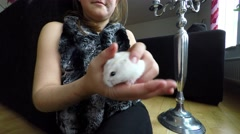 Girl playing with little white hamster - stock footage