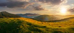 Agricultural field in mountains at sunset Stock Photos