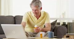 Senior man checking laptop for digital prescription Stock Footage