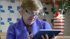 Elderly woman relaxing with a tablet computer in her kitchen Stock Footage