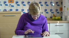 old woman typing on the touch screen of a tablet computer: composing a message - stock footage