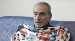 sick old man with fever and cold: sitting on the sofa with blanket - stock footage
