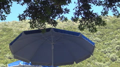 Relaxing place with shadow from tree and umbrella on the seashore. Summer day. Stock Footage
