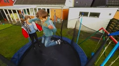 Kids jumping on a trampoline in the garden - slowmotion Stock Footage