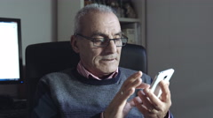 old man composing a sms or chat message with modern mobile phone - stock footage