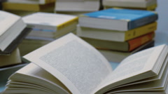 Stacked books opened on a table - tracking shot Stock Footage
