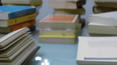 Tracking shot of stacked books on a table Stock Footage