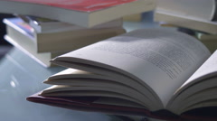 Tracking shot of books opened on a table: learning, culture, student Stock Footage