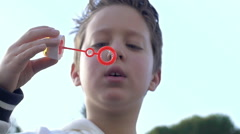 Child making bubble blower: rallenty, slow motion  Stock Footage