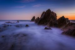 Long exposure of waves crashing on rocks at sunset, in Corona del Mar, Califo Stock Photos