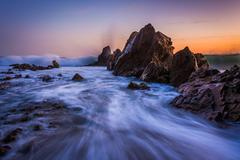 Waves crashing on rocks at sunset, in Corona del Mar, California. Stock Photos