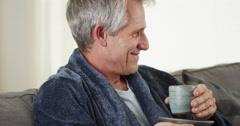 Senior man looking at camera with tea Stock Footage