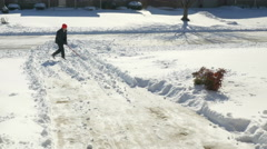 Middle aged man clearing snow from driveway - stock footage